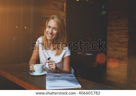 Attractive happy hipster girl with good mood posing while sitting alone in modern coffee shop interior, cheerful Caucasian woman with beautiful smile enjoying her recreation time in cozy cafe bar  - stock photo