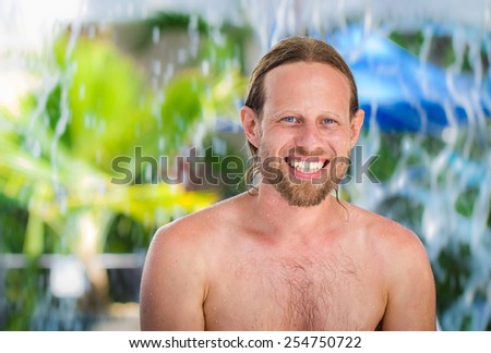 Attractive, happy man at resort swimming pool - stock photo