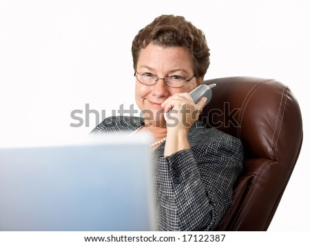 Attractive, happy mature businesswoman at work on the phone - stock photo