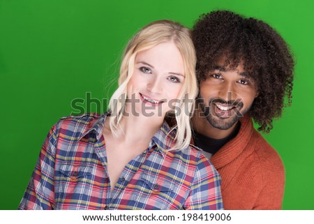 Attractive happy multiethnic couple posing close together in an affectionate intimate embrace smiling at the camera - stock photo