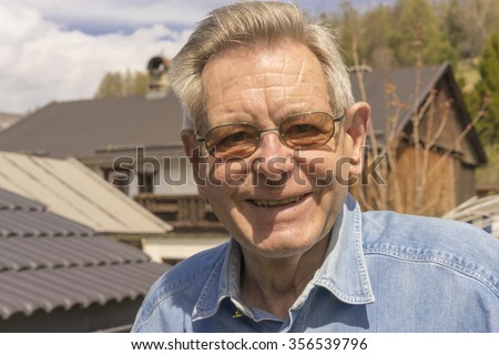 Attractive happy senior man wearing glasses standing outdoors in his garden smiling at the camera, close up head and shoulders portrait - stock photo