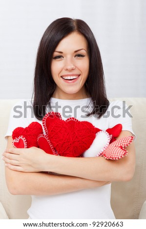Attractive happy smiling brunette young girl holding lot of red valentine heart, woman sitting on couch at home, concept of valentine's day love - stock photo