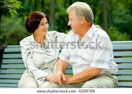Attractive happy smiling senior couple embracing outdoors - stock photo