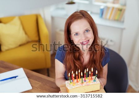 Attractive happy woman celebrating her birthday sitting at the dining table holding a cake with burning candles and looking up at the camera with a lovely smile of pleasure - stock photo