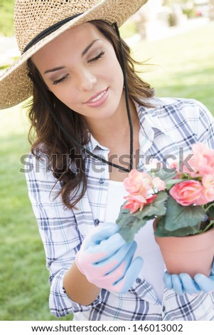Attractive Happy Young Adult Woman Wearing Hat Gardening Outdoors.