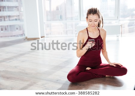 Attractive happy young woman doing yoga and using cell phone sitting on the floor - stock photo
