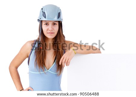 Attractive happy young woman in climbing equipment holding a blank banner isolated in white