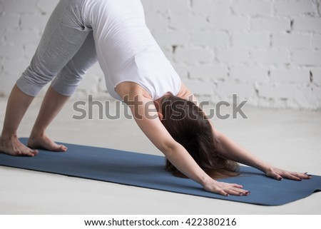 Attractive happy young woman working out indoors. Beautiful model doing exercises on blue mat in room with white walls. Standing in downward facing dog pose (adho mukha svanasana) - stock photo