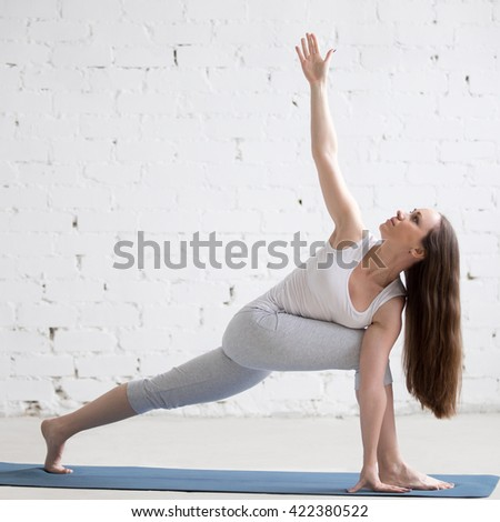 Attractive happy young woman working out indoors. Beautiful model doing exercises on blue mat in room with white walls. Twisting Side Angle Pose, Parivrtta Parsvakonasana. Full length. Square image - stock photo