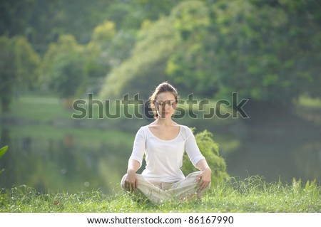 Attractive Healthy Asian Woman meditating in the park - stock photo