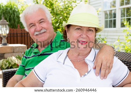Attractive healthy happy senior couple sitting arm in arm on an outdoor summer patio in front of their home smiling warmly at the camera - stock photo