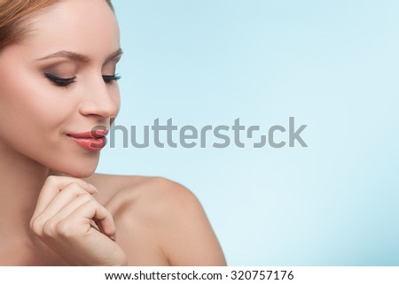 Attractive healthy woman is standing and posing. She is touching her chin gently and smiling. Her eyes are closed with joy. Isolated on blue background and copy space in right side - stock photo