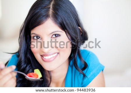 attractive healthy young woman eating fruit salad - stock photo