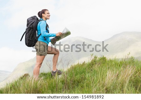 Attractive hiker with backpack hiking uphill holding a map in the countryside - stock photo