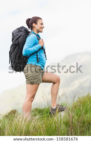 Attractive hiker with backpack walking uphill in the countryside