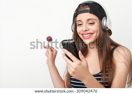 Attractive hipster girl is using mobile phone with fun. She is listening to music from headphones and smiling. The lady is eating lollipop with pleasure. Isolated and copy space in left side - stock photo