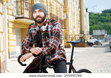Attractive hipster guy with hat and headphones is sitting on bicycle with joy. He is smiling - stock photo