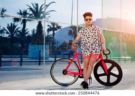 Attractive hipster man standing with his fixed gear bike outdoors, fashionable cute man posing with bicycle at sunny evening - stock photo