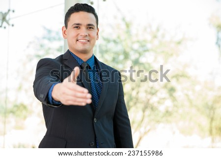 Attractive Hispanic businessman extending his hand for a handshake and smiling - stock photo