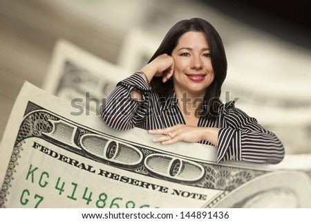 Attractive Hispanic Woman Leaning on a One Hundred Dollar Bill.