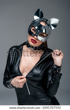 Attractive hot girl unzipping catsuit isolated on grey & Attractive Hot Girl Unzipping Catsuit Isolated Stock Photo (Edit Now ...