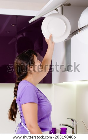 Attractive housewife doing the dishes standing at the kitchen sink reaching up to replace a dinner plate in storage in a rack in a cupboard - stock photo