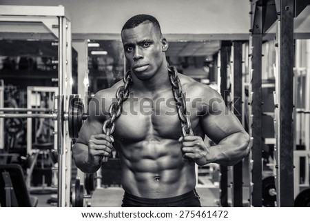 Attractive hunky black male bodybuilder doing bodybuilding pose in gym with iron chains over shoulders - stock photo