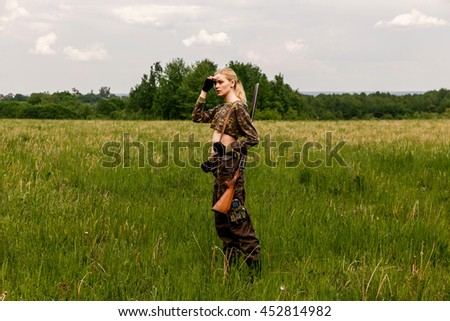 Attractive hunter girl with hunting double-barreled rifle looking out the trophy