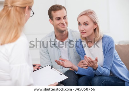 Attractive husband and wife are visiting a psychologist. The woman is trying to explain something to therapist with aspiration. The man is looking at her with love and smiling - stock photo