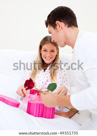 Attractive husband giving a present to his wife in the bedroom