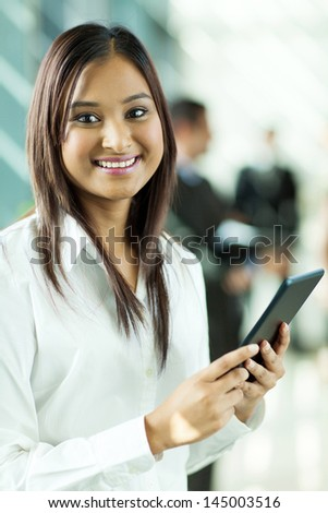 attractive indian office worker holding tablet computer in office - stock photo
