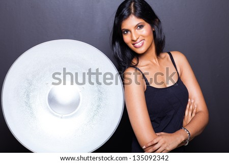 attractive indian woman posing next to beauty dish on black background - stock photo