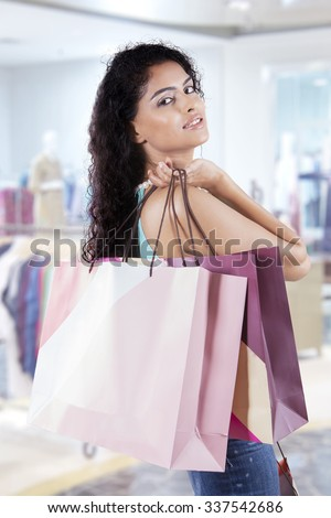 Attractive indian woman with curly hair, carrying shopping bags in the shopping mall - stock photo