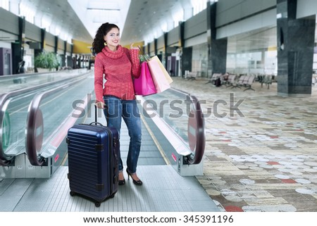 Attractive indian woman with winter clothes, standing in the airport hall while holding suitcase and shopping bags - stock photo