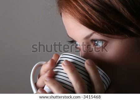 Attractive lady drinking hot beverage. Short DOF. Sharp striking eyes - stock photo