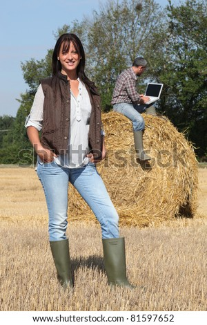 Attractive lady farmer standing in front of her husband on a haystack using a laptop with the screen left blank - stock photo