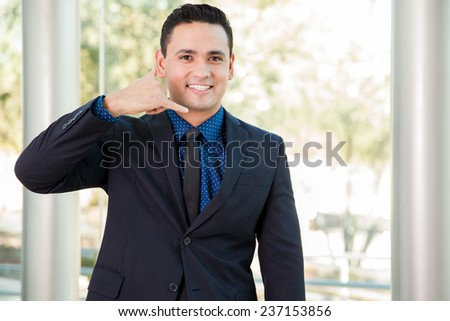 Attractive Latin businessman inviting customers to call and do business - stock photo