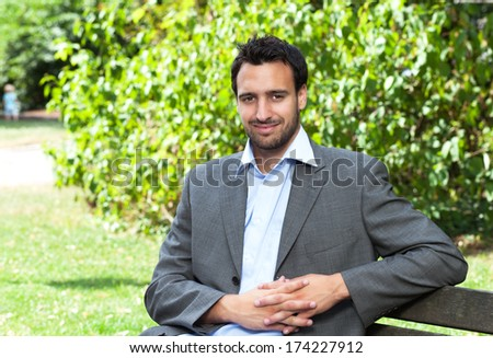 Attractive latin businessman relaxing in a park  - stock photo