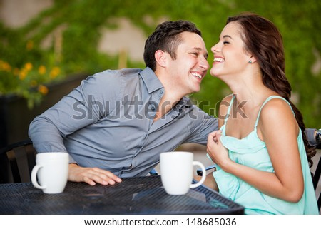 Attractive Latin couple laughing and having fun on a date at a restaurant