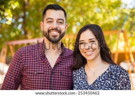 Attractive Latin young couple enjoying a sunny day outdoors and smiling - stock photo