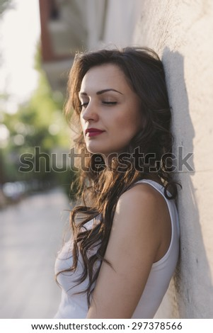 Attractive laughing female standing against wall background