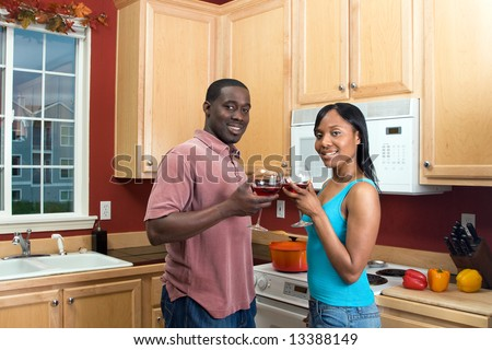 Attractive laughing young African American couple standing in a kitchen clinking wine glasses, in a toast.  Horizontally framed shot with the man and woman looking at the camera.