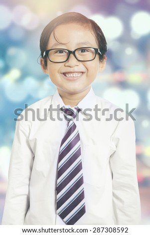 Attractive little entrepreneur smiling on the camera, shot with bokeh background - stock photo