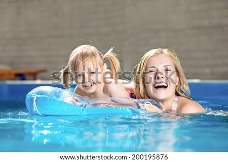 Attractive little girl and her mother swimming in water pool - stock photo