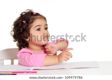Attractive little girl draws with colored pencils sitting at the table