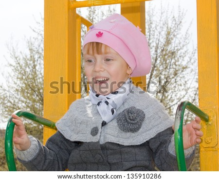 Attractive little girl on outdoor playground equipment - stock photo