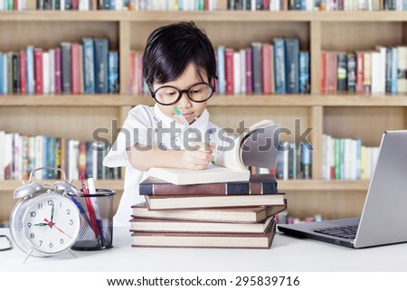 Attractive little girl studying in the library while wearing glasses and writing on the book - stock photo