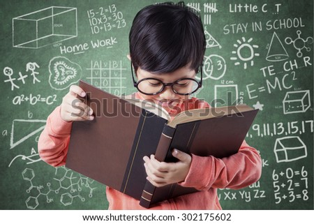 Attractive little girl wearing glasses and casual clothes in the class while reading a literature near the blackboard - stock photo
