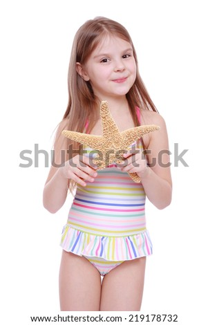 attractive little girl wearing pink swimsuit holding big sea star isolated