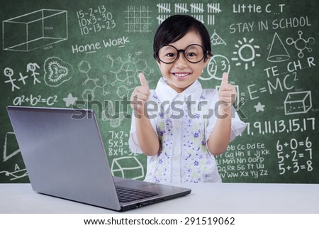 Attractive little girl with laptop in class, wearing glasses and showing thumbs up with scribble background - stock photo